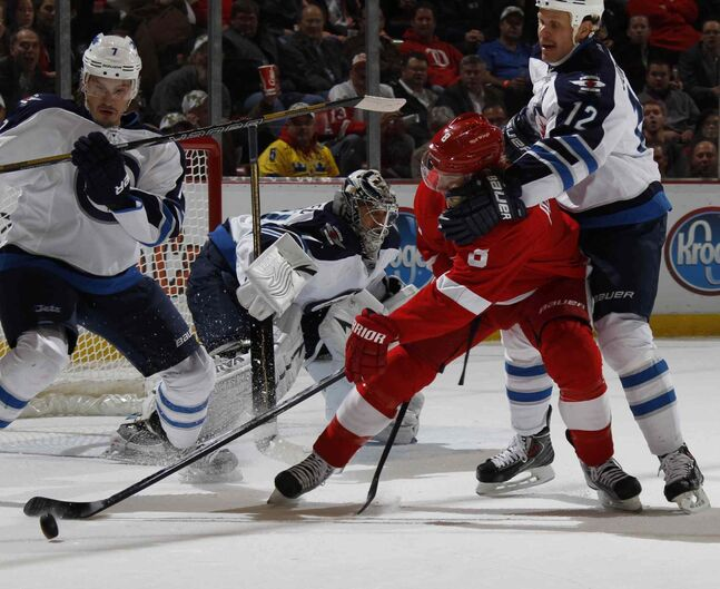 Detroit Red Wings' Justin Abdelkader is grabbed from behind by Winnipeg Jets forward Olli Jokinen during the first period.