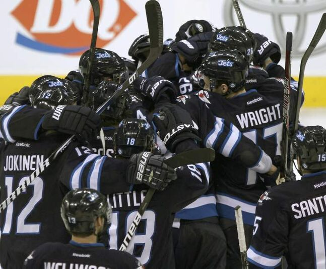 Winnipeg Jets players mob captain Andrew Ladd after his shootout goal sealed the deal against the Tampa Bay Lightning.