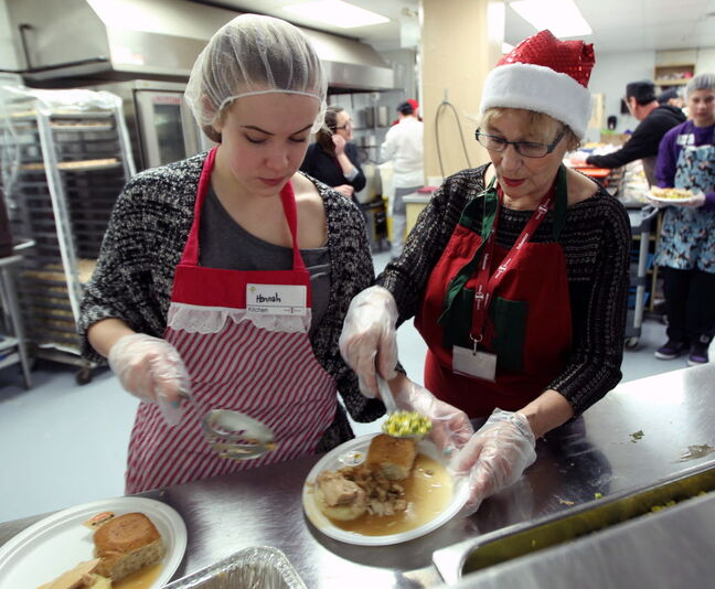 Volunteers Hannah Taylor, left, and Carol Cockrell work hard in the kitchen at Siloam Mission to prepare Christmas Eve dinner Tuesday.