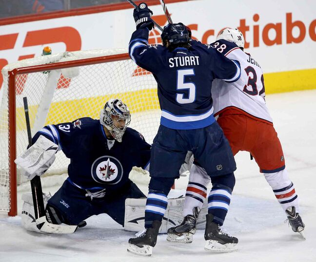 Winnipeg Jets' goaltender Ondrej Pavelec (31) stops a bouncing puck with Mark Stuart (5) and Columbus Blue Jackets' Boone Jenner (38) in front of the net during the first period at Winnipeg's MTS Centre Saturday.