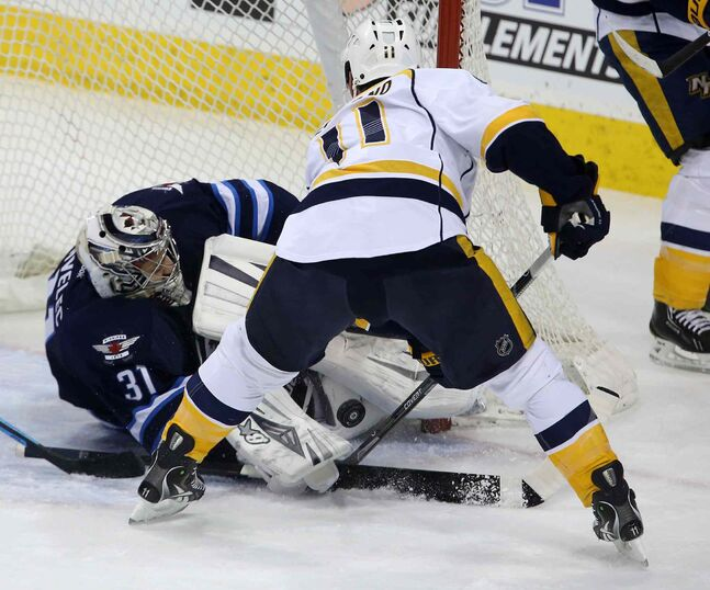 Winnipeg Jets' goaltender Ondrej Pavelec (31) stops Nashville Predators' David Legwand (11) right in front of the net during first period in Winnipeg Tuesday.