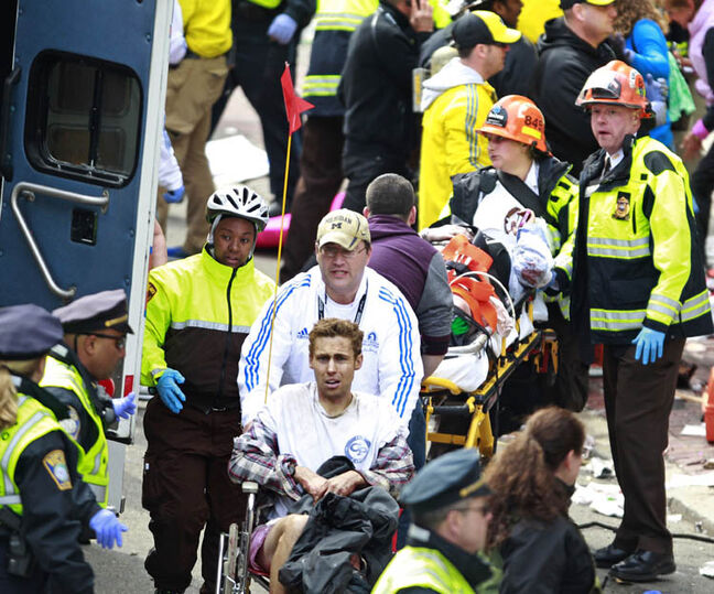 Medical workers aid injured people at the finish line of the 2013 Boston Marathon following an explosion in Boston, Monday, April 15, 2013. Two explosions near the finish of the Boston Marathon on Monday, killing at least  two people, injuring over 20 others.