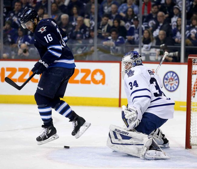 Winnipeg Jets' Andrew Ladd (16) jumps over a shot by Bryan Little (18), not shown, that gets past Toronto Maple Leafs' goaltender James Reimer (34) during second period at MTS Centre in Winnipeg Saturday.