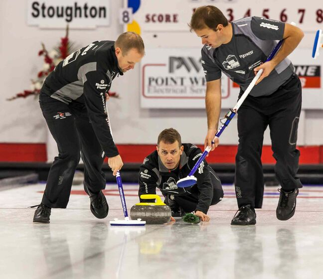 Mark Nichols (left) and Reid Carruthers sweep while Jeff Stoughton follows his delivery.
