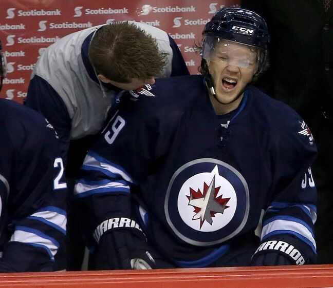 Winnipeg Jets' Tobias Enstrom (39) reacts after being hit by one of the Buffalo Sabres during first period NHL hockey action in Winnipeg. 