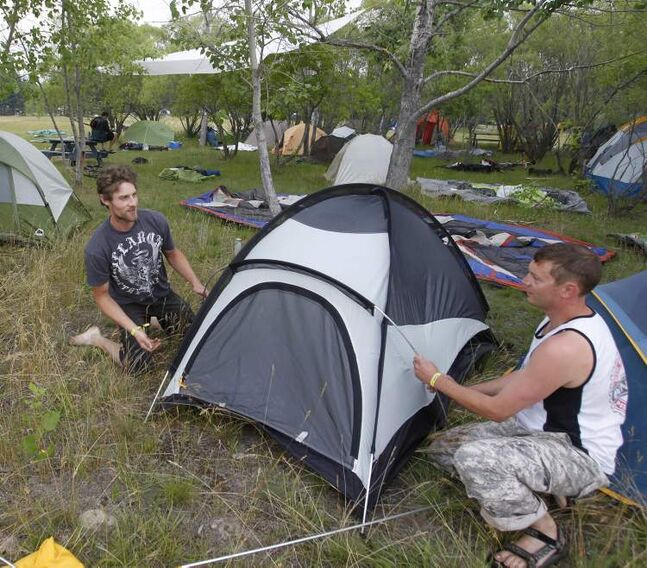 Jody Hopper (right) helps his friend Sean Strachan set up his tent in the festival camping.