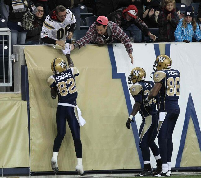 Winnipeg Blue Bombers Terrence Edwards (left) gets a high five from fans as teammates Will Ford (centre) and Akkeem Foster look on after Edwards scored a touchdown against the Edmonton Eskimos during the first quarter of Friday night's game.