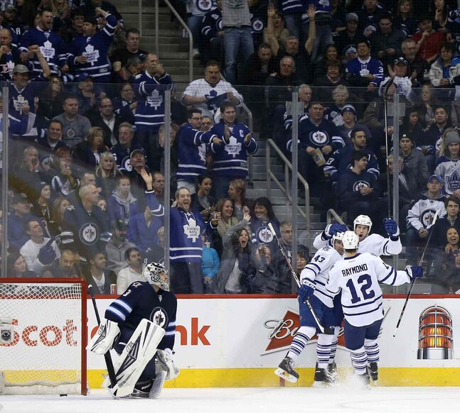 Winnipeg Jets' goaltender Ondrej Pavelec (31) looks on as Toronto Maple Leafs' Nazem Kadri (43), Mason Raymond (12) and Troy Bodie (40) celebrate Bodie's second-period goal during Saturday's game at Winnipeg's MTS Centre.