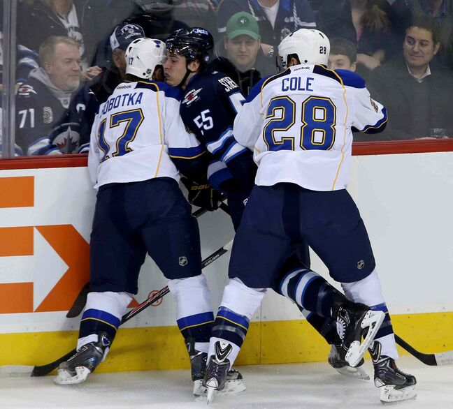 St. Louis Blues' Vladimir Sobotka (17) and Ian Cole sandwich Winnipeg Jets' Mark Scheifele during the first period.