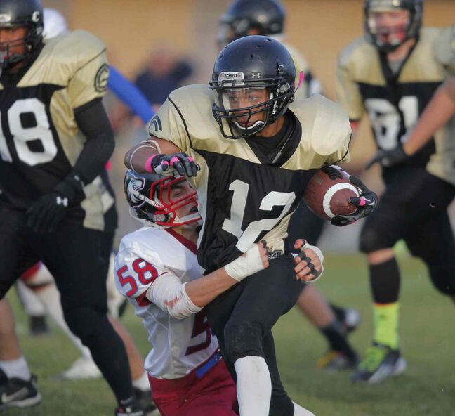 Devon Taylor (12) of the Fighting Gophers struggles to get free from the grip of the Huskies' Elliott Ormonde (58).