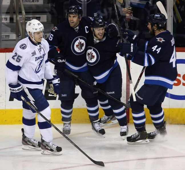 Winnipeg Jets' Andrew Ladd (16), Bryan Little (18) and Zach Bogosian celebrate after Ladd opened the scoring against the Tampa Bay Lightning as Lightnings' Matthew Carle skates past.