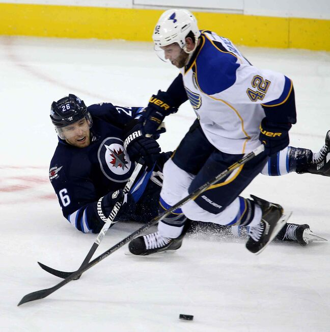 Winnipeg Jets forward Blake Wheeler trips and has the puck stolen by St. Louis Blues forward David Backes during the third period.