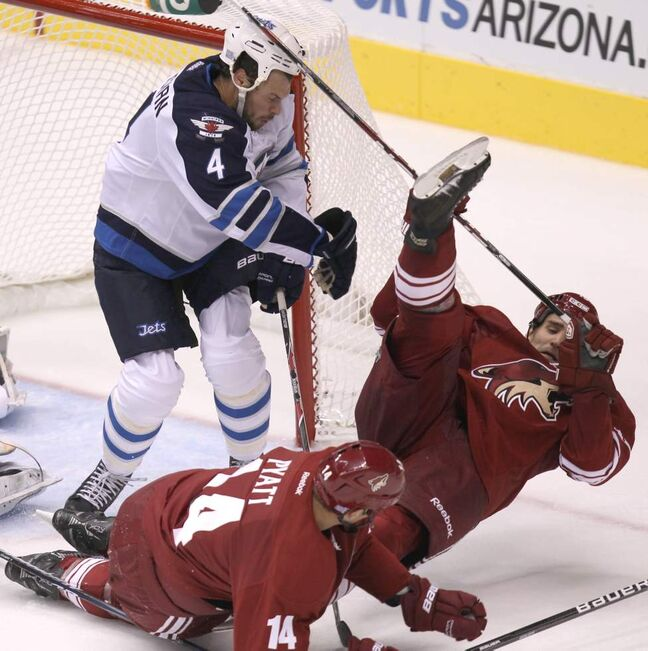 Winnipeg Jets' Zach Bogosian clears Phoenix Coyotes' Boyd Gordon  from the front of the net during second period action at the Jobing.com Arena in Glendale, Arizona. The Coyotes beat the Winnipeg Jets 4-1.   (JOE BRYKSA / WINNIPEG FREE PRESS)