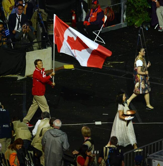 Simon Whitfield of Canada marches during the opening ceremony of the London 2012 Olympic Games is held at the Olympic Stadium in London England, July 27, 2012.