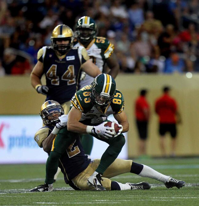 Winnipeg Blue Bombers' Matt Bucknor hangs on tight to tackle  Edmonton Eskimos' #85 Nate Coehoorn in the third quarter Thursday evening at Investors Group Field.