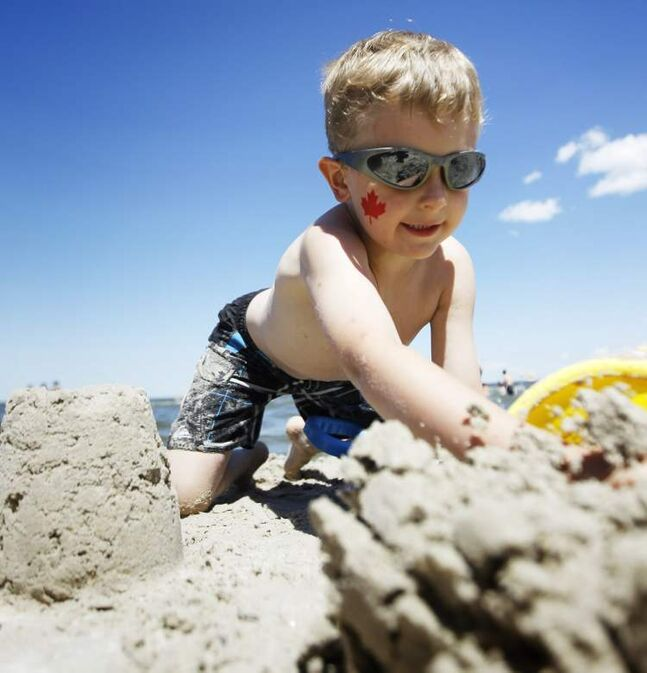 Five-year-old Benji Pepper smashes a sand castle in the sunshine at Grand Beach on Canada Day.
