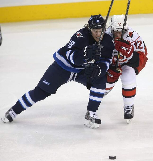 Winnipeg Jets' Bryan Little and Carolina Hurricanes' Eric Staal battle for the puck during the first period.