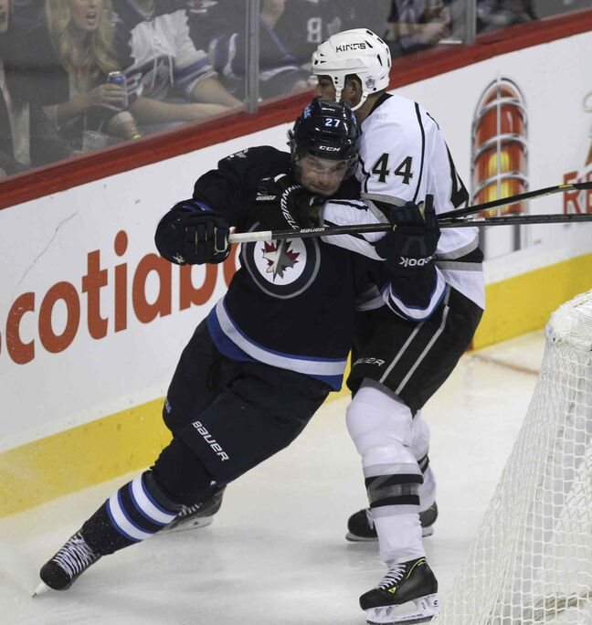 Winnipeg Jets' Eric Tangradi (27) is held back during a scramble behind the net by Los Angeles Kings' Robyn Regehr (44) in the third period.