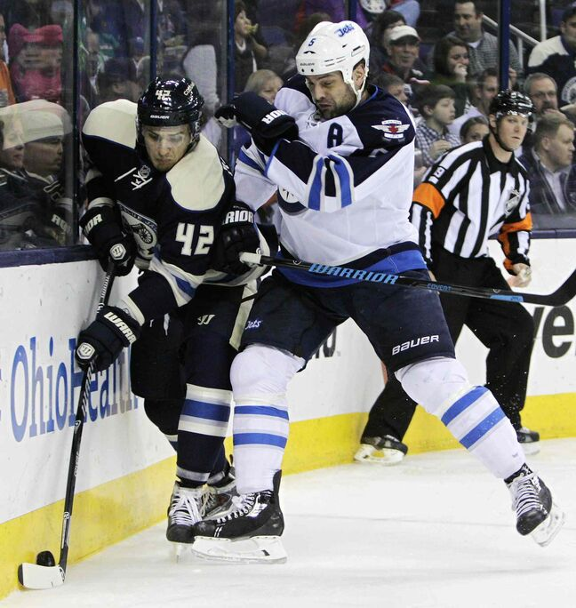 Jets defenceman Mark Stuart crushes Columbus' Artem Anisimov Monday night.