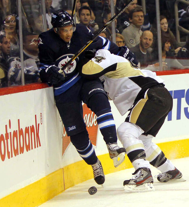 Jets' Evander Kane gets crunched into the boards by Penguins' Brooks Orpik