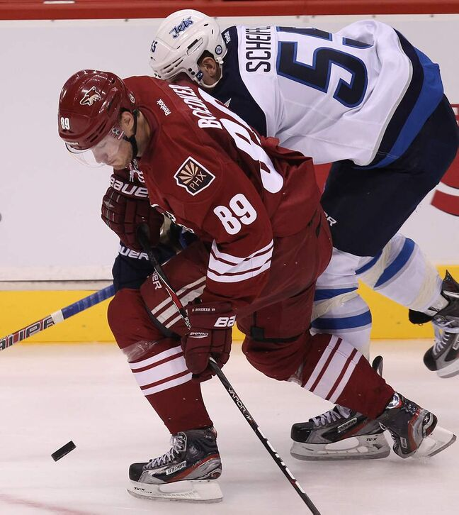 Winnipeg Jets' Mark Scheifele, rear, tries to catch up with Phoenix Coyotes' Mikkel Boedker during third period action at the Jobing.com Arena in Glendale, Arizona. The Coyotes beat the Winnipeg Jets 4-1.   (JOE BRYKSA / WINNIPEG FREE PRESS)