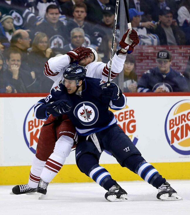 Jets forward Blake Wheeler lays the body on Phoenix Coyotes David Moss.