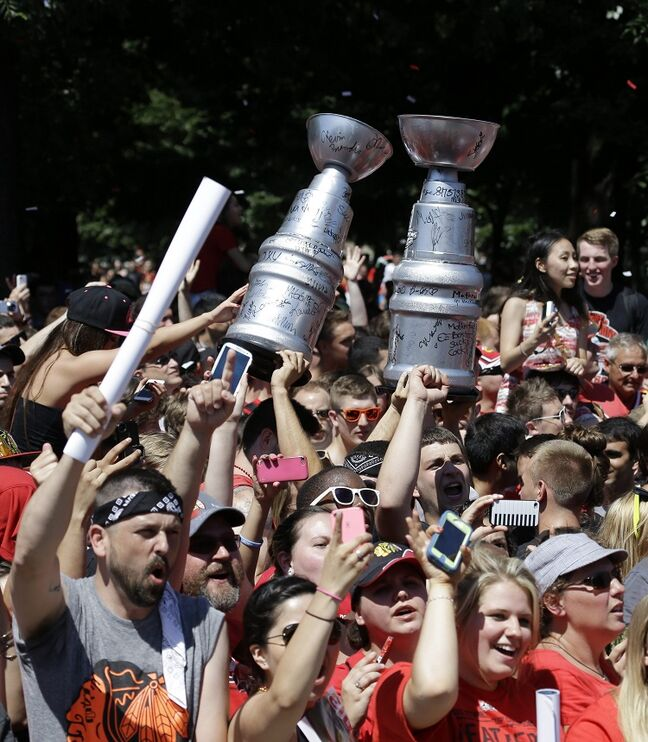 Fans cheer along the parade route wielding homemade Stanley Cups as buses carrying the Chicago Blackhawks pass.