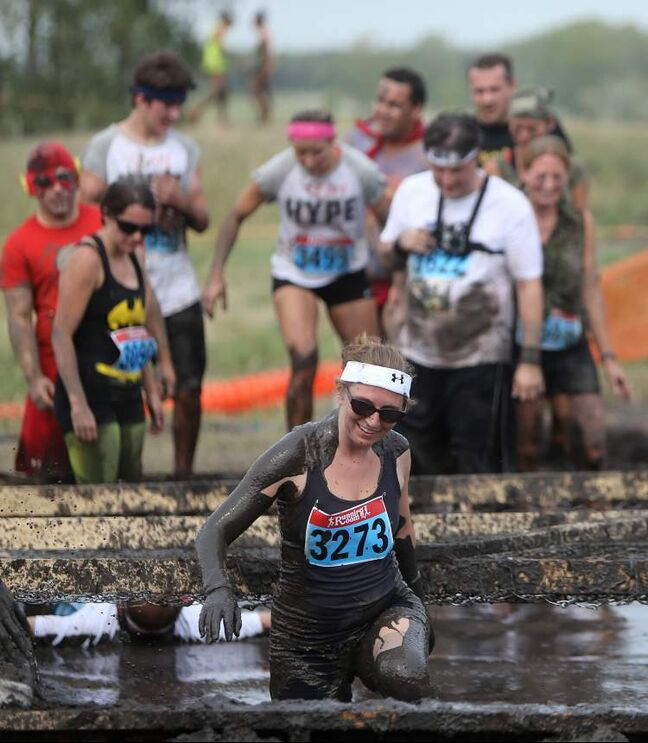 A participant wades through some mud.