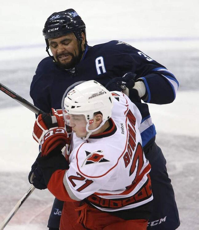 Winnipeg Jets' Dustin Byfuglien (33) bumps Carolina Hurricanes' Drayson Bowman (21) at centre ice during the third period.