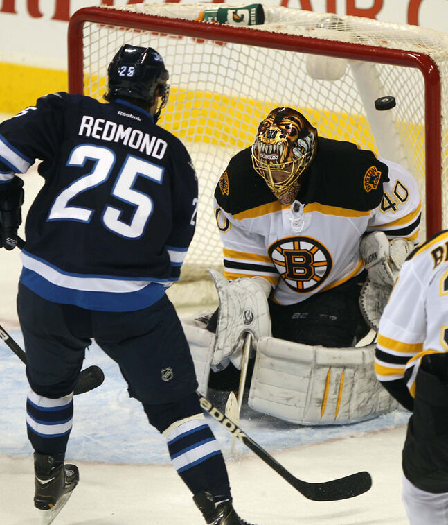 Winnipeg Jets Zach Redmond gives chase as the puck flies through the crease, but not across the goal line, past Boston Bruins goaltender Tuukka Rask milliseconds after the final buzzer sounded at the MTS Centre.