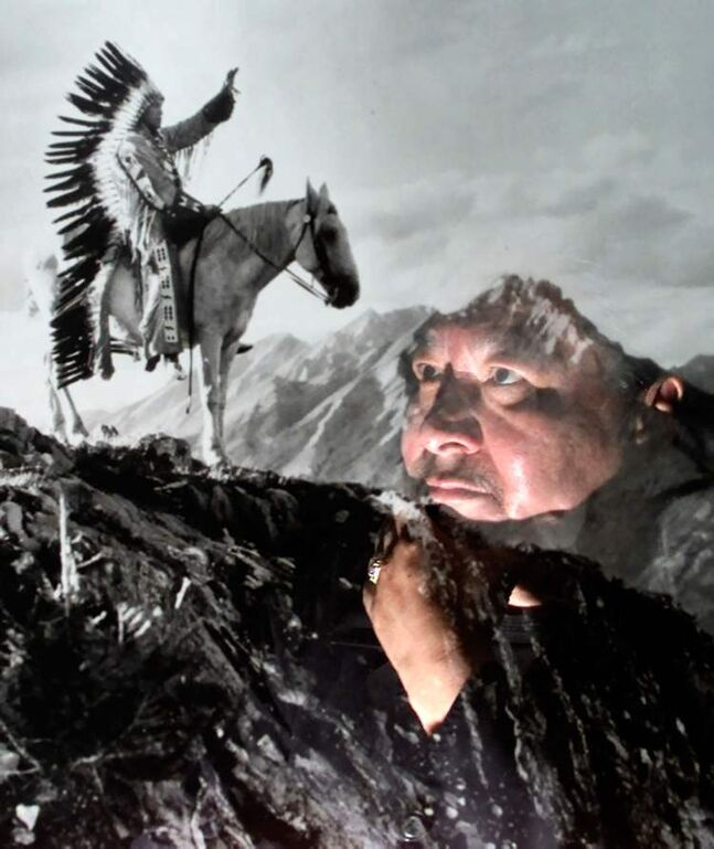 Indian Claims Commissioner Elijah Harper appears to be peering at a horse mounted Indian in full headress from the side of a mountain, as he is reflected in the picture that is on his office wall in Ottawa in 2000.