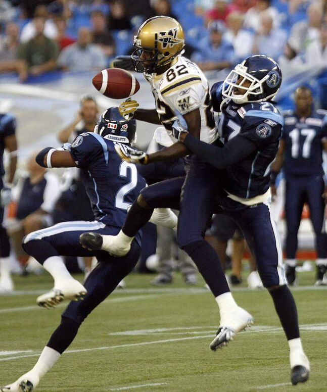 Toronto Argonauts' Orlondo Steinauer, left, and Kenny Heatly, right, put pressure on Winnipeg Blue Bombers wide receiver Terrence Edwards (82) who missed catching the pass during their Canadian Football League game in Toronto, August 1,  2008.  THE CANADIAN PRESS/J.P. Moczulski
