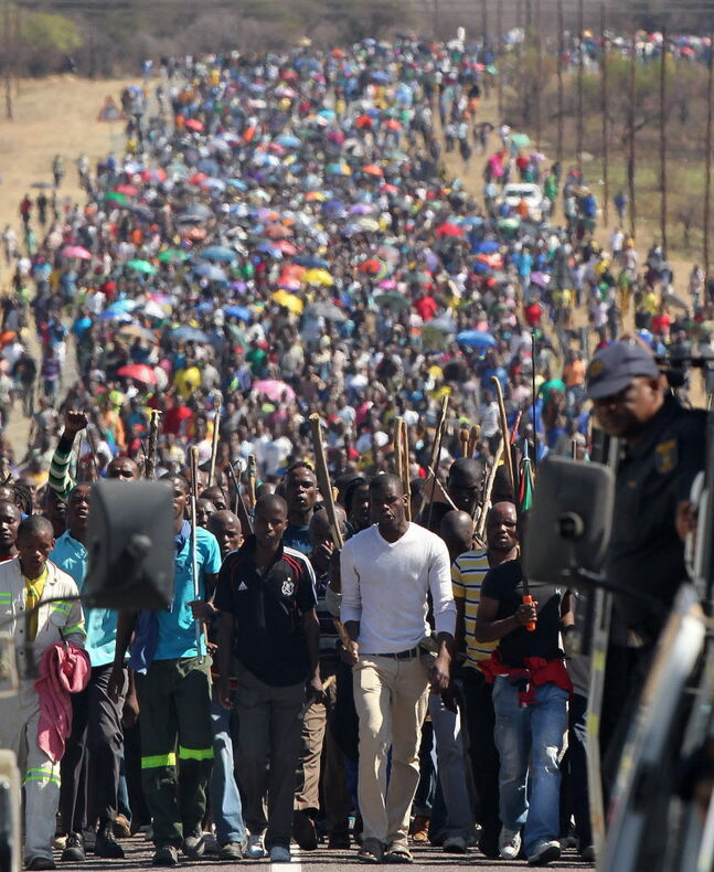 Miners march to Lonmin Platinum Mine near Rustenburg, South Africa, in an attempt to stop operations. Union rivalry is at the root of violent illegal strikes that have been troubling the mining industry that is the engine driving Africa's largest economy. (AP Photo/Themba Hadebe)