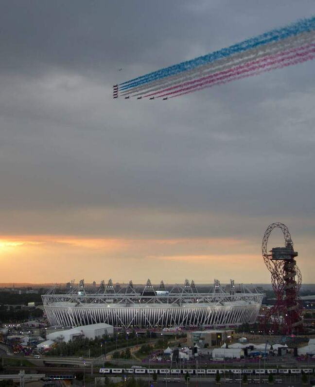 The Red Arrows aerobatic team flies over the Olympic Stadium ahead of the Opening Ceremony of the 2012 Summer Olympics, Friday, July 27, 2012, in London.