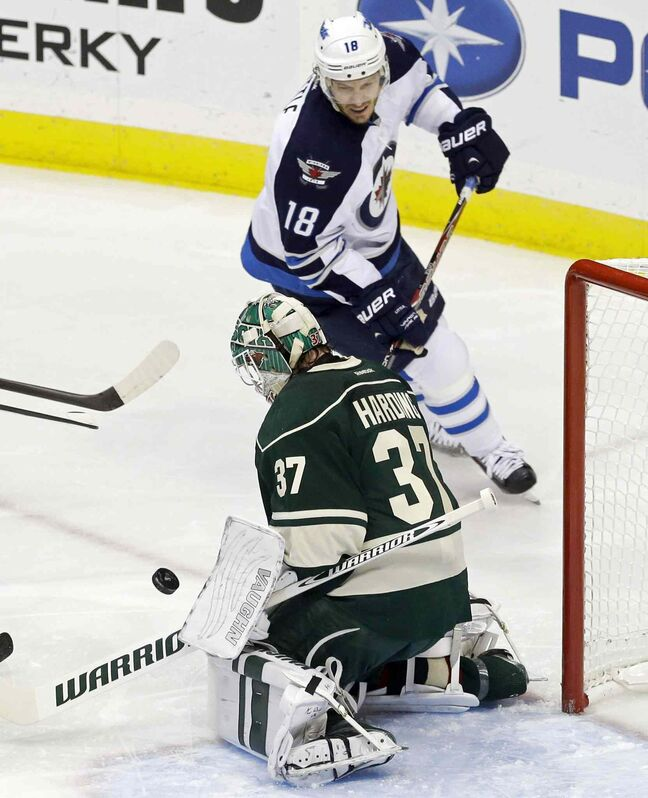 Bryan Little of the Winnipeg Jets races in for the rebound as Minnesota Wild goalie Josh Harding stops a shot in the first period.