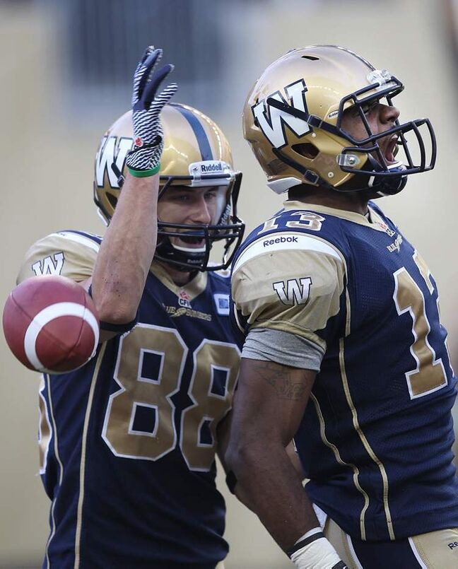 Winnipeg Blue Bombers' Chris Matthews (right) celebrates the team's first-ever touchdown in the new stadium with teammate Jade Etienne.
