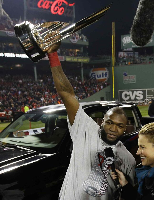 Boston Red Sox designated hitter David Ortiz holds up the MVP trophy while being interviewed.