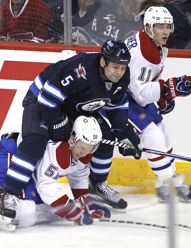 Winnipeg Jets' Mark Stuart ends up on top of Montreal Canadiens' David Desharnais (51) in the first period Thursday night.