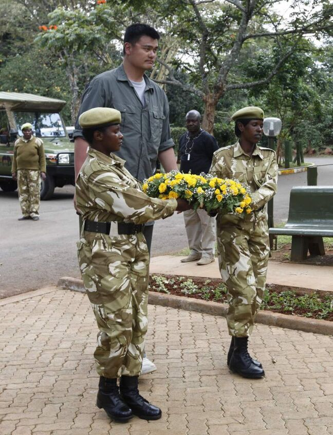 Yao Ming, China's top basketball star, follows Kenya Wildlife Rangers to lay a wreath on the memorial site of the Kenya Wildlife Rangers killed during fighting with poachers in Nairobi. Ming is visiting Kenya on his first-ever visit to Africa to film a documentary aimed at reducing poaching attacks against elephants and rhinos. The two animals are coming under increasing attacks by poachers who sell rhino horns and elephant tusks to buyers in Asia who acquire the animal products as a sign of affluence. (AP Photo/Sayyid Azim)