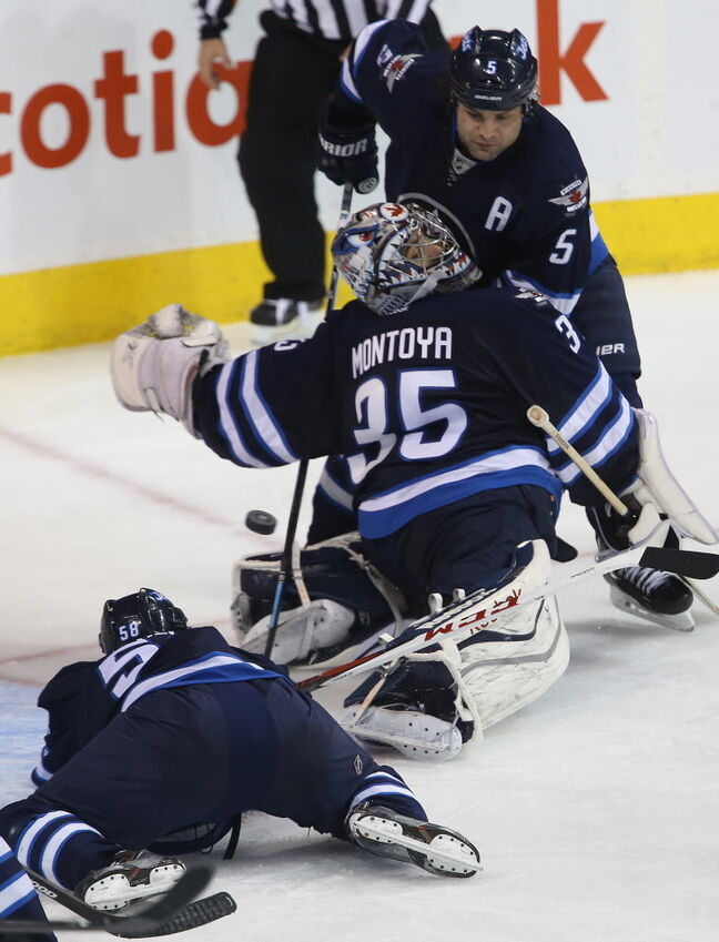 Winnipeg Jets' Eric O'Dell (58), goaltender Al Montoya (35) and Mark Stuart (5) watch a puck that gets past the net minder, but doesn't make it to the net against the Carolina Hurricanes' during the third period.