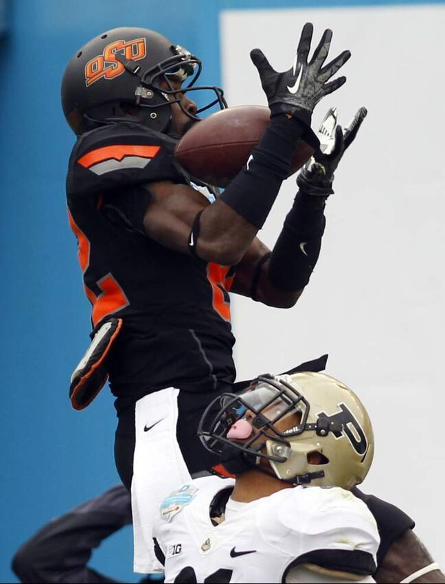 Oklahoma State Cowboys wide receiver Isaiah Anderson (82) pulls in a touchdown pass over Purdue Boilermakers cornerback Ricardo Allen (21) during the Heart of Dallas Bowl on Tuesday in Dallas, Texas. The Oklahoma State Cowboys defeated the Purdue Boilermakers, 58-14. (Richard W. Rodriguez/Star-Telegram/MCT)