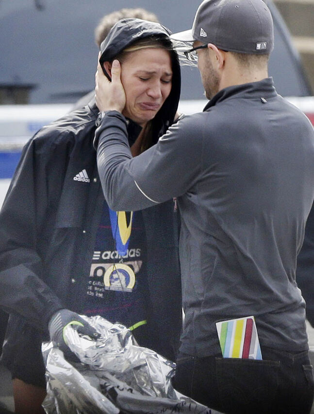 An unidentified Boston Marathon runner is comforted as she cries in the aftermath of two blasts which exploded near the finish line of the Boston Marathon in Boston, Monday, April 15, 2013.