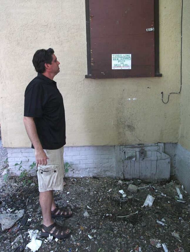 Landlord Steve Tait looks at a rear window in his Furby Street rooming house. A former tenant  who was evicted used the window for drive-by drug service. The next tenant had to post signs to stop knocking from past customers.