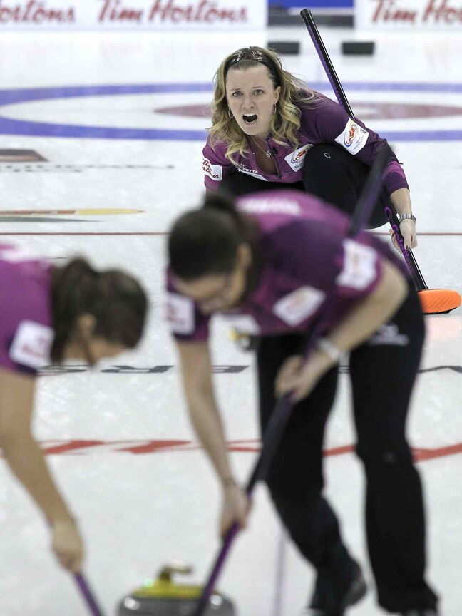Skip Chelsea Carey (top) yells to her sweepers in her team's game against the Jennifer Jones rink.