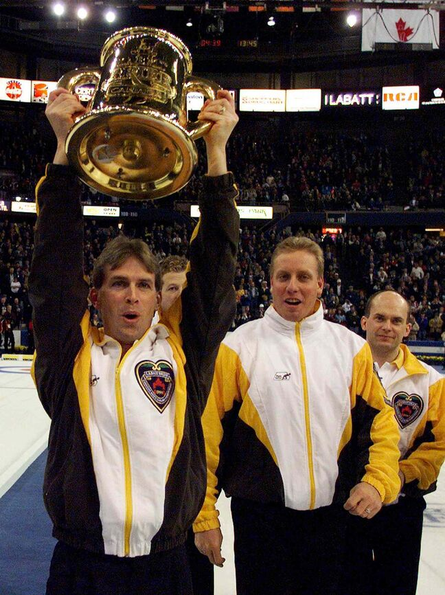 Manitoba skip Jeff Stoughton celebrates as he carries the Labatt Brier tankard up the ice after he and his rink beat Quebec 9-5 in the final in 1999 at left is team fifth Steve Gould and third Jonathan Mead at right.