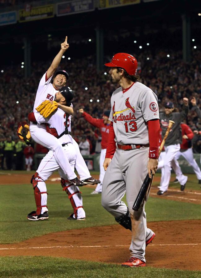 The St. Louis Cardinals' Matt Carpenter (right) walks off after striking out to end the game as the the Boston Red Sox begin to celebrate their World Series win.