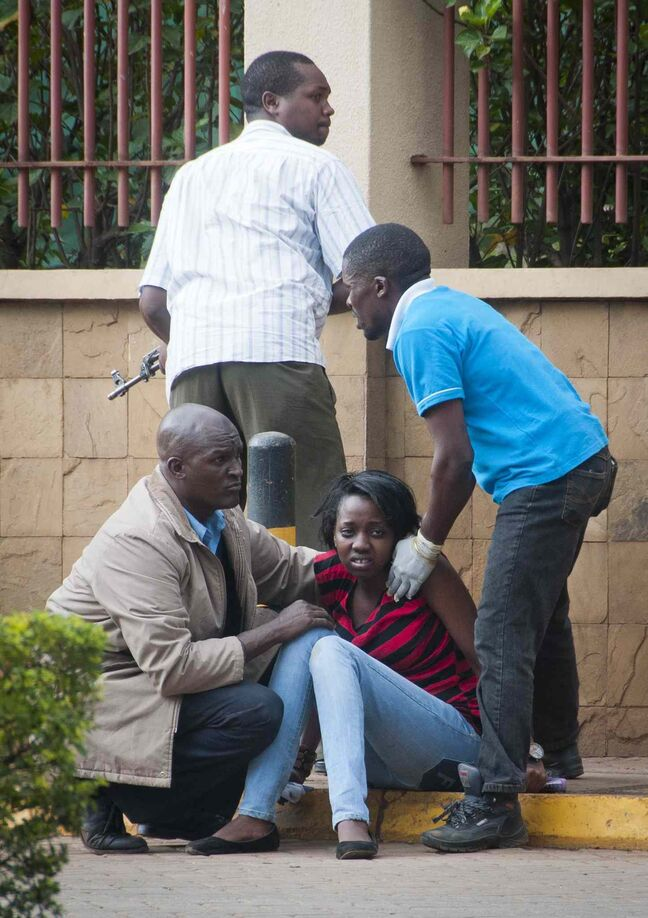 A woman who had been hiding inside and then managed to flee, sits in a state of shock, as a member of the security force keeps watch outside the Westgate Mall in Nairobi, Kenya, Saturday. Gunmen threw grenades and opened fire Saturday killing at least 22 people in an attack targeting non-Muslims at an upscale mall in Kenya's capital that was hosting a children's day event, a Red Cross official and witnesses said.