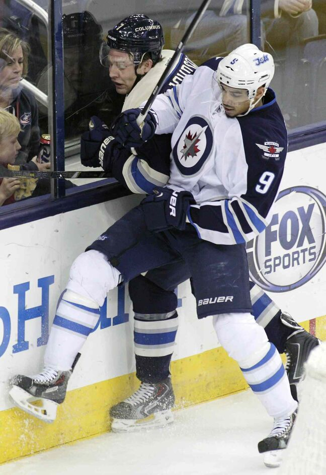 Evander Kane checks the Blue Jackets' Jack Johnson Monday night.