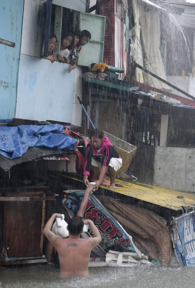 A man gives hot drinks and food to people staying inside their flooded homes in Quezon City, north of Manila, Philippines, on Tuesday Aug. 7, 2012. Relentless rains submerged half of the sprawling Philippine capital, triggered a landslide that killed several people and sent emergency crews scrambling Tuesday to rescue and evacuate tens of thousands of residents.  AP Photo / Aaron Favila