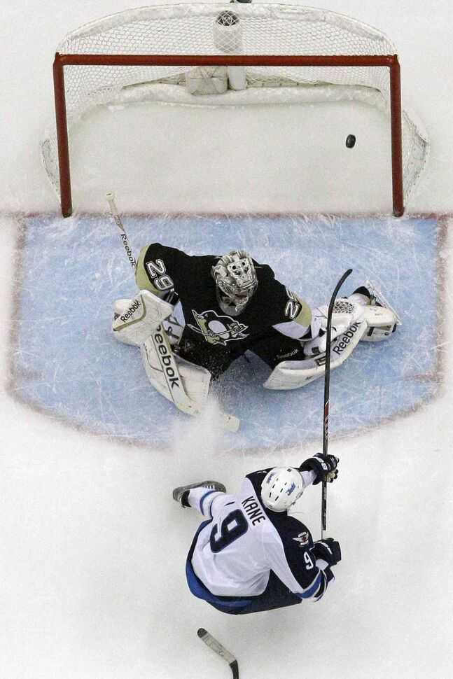 Jets forward Evander Kane backhands a shot past Penguins goalie Marc-Andre Fleury for the first of two goals in the second period.